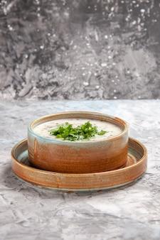 흰색 테이블 유제품 우유 수프 접시에 채소를 곁들인 맛있는 도브가 요구르트 수프 전면 보기