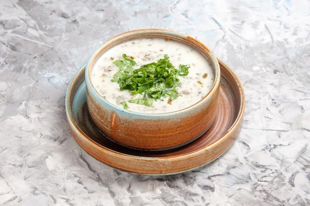 正面図白いテーブルの上の緑のおいしいdovgaヨーグルトスープミルクスープ食事皿