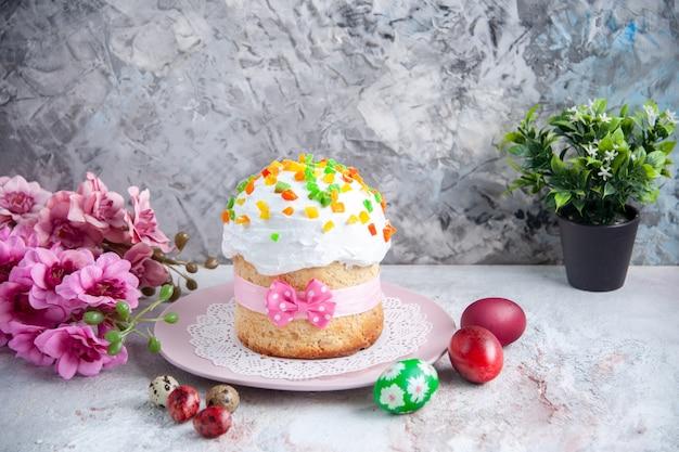 Вид спереди вкусный пасхальный торт с крашеными яйцами внутри тарелки на белой поверхности десерт сладкий богато украшенный пасхальный красочный пирог