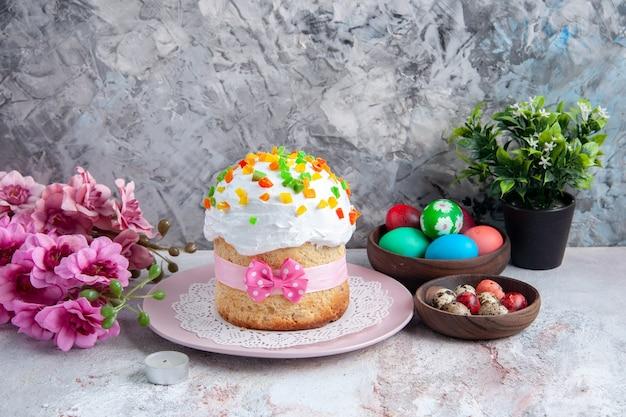 Вид спереди вкусный пасхальный торт с крашеными яйцами внутри тарелки на белой поверхности десерт сладкий богато украшенный пасхальный красочный весенний пирог