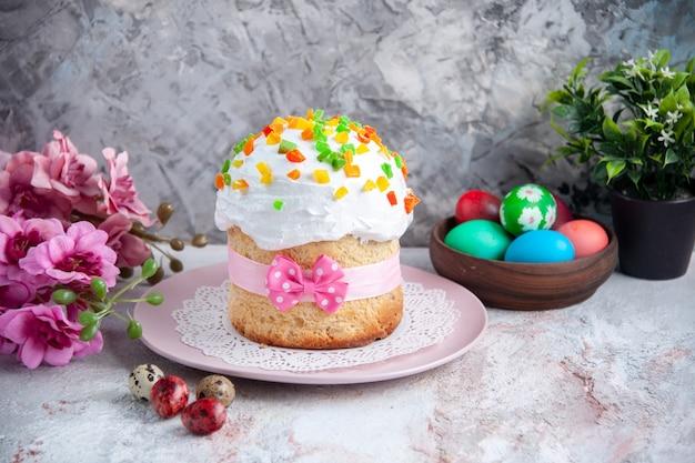Вид спереди вкусный пасхальный торт с крашеными яйцами внутри тарелки на белой поверхности десерт сладкий богато украшенный пасхальный весенний пирог