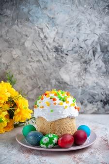Вид спереди вкусный пасхальный пирог с крашеными яйцами внутри тарелки на белой поверхности весенний десертный пирог богато украшенный пасхальный красочный сладкий
