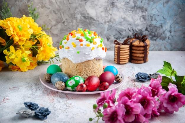 Вид спереди вкусный пасхальный пирог с крашеными яйцами внутри тарелки на белой поверхности весенний десертный пирог богато украшенный пасхальный красочный