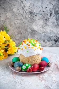 Вид спереди вкусный пасхальный пирог с крашеными яйцами внутри тарелки на белой поверхности весенний десертный пирог богато украшенный пасхальный сладкий