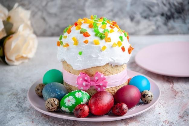 Вид спереди вкусный пасхальный торт с крашеными яйцами внутри тарелки на белой поверхности весенний пирог красочный сладкий десерт богато украшенный