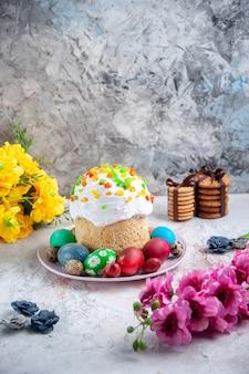 Вид спереди вкусный пасхальный торт с крашеными яйцами внутри тарелки на белой поверхности весенний пирог богато украшенный пасхальный красочный сладкий десерт