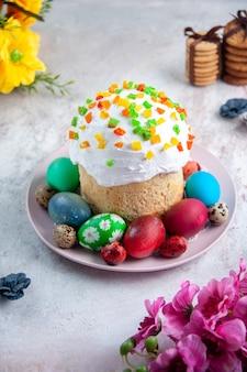 Вид спереди вкусный пасхальный кулич с крашеными яйцами внутри тарелки на белой поверхности весенний пирог богато украшенный пасхальный сладкий десерт