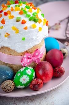 Вид спереди вкусный пасхальный пирог с крашеными яйцами внутри тарелки на белой поверхности сладкий пирог пасха красочный десерт богато украшенный весна