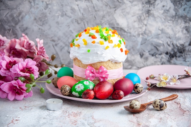 Вид спереди вкусный пасхальный кулич с крашеными яйцами внутри тарелки на белой поверхности сладкий пирог пасхальный десерт богато украшенная весна Premium Фотографии