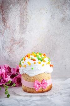 Вид спереди вкусный пасхальный торт со сливками и сухофруктами на белой поверхности пасха красочная весенняя концепция богато украшенный цвет десерта