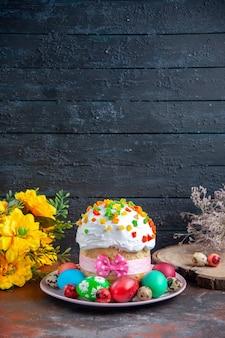 Вид спереди вкусный пасхальный кулич с крашеными крашеными яйцами и желтыми цветами на темном фоне десерт весна богато украшенная сладкая красочная группа пасха
