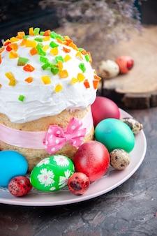 Вид спереди вкусный пасхальный кулич с крашеными крашеными яйцами и желтыми цветами на темном фоне десерт весна богато украшенный сладкий красочный мульти пасха