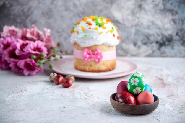 Вид спереди вкусный пасхальный торт с крашеными яйцами внутри тарелки на белой поверхности десерт весна сладкая пасха красочные богато украшенные мульти группа