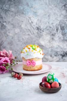 Вид спереди вкусный пасхальный торт с крашеными яйцами внутри тарелки на белой поверхности десерт весна сладкая пасха красочный пирог мульти группа