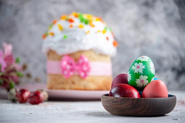 Вид спереди вкусный пасхальный торт с крашеными яйцами внутри тарелки на белой поверхности десерт весна сладкая пасха красочный пирог богато украшенный мульти группа