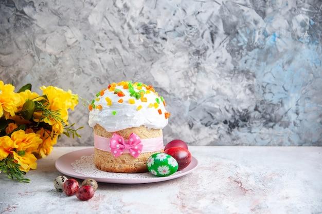 Вид спереди вкусный пасхальный пирог с крашеными яйцами внутри тарелки на белой поверхности десерт весна сладкая пасха красочный пирог богато украшенный