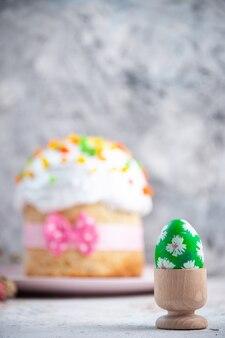 Вид спереди вкусный пасхальный пирог с расписным зеленым яйцом внутри яичной чашки на белой поверхности десерт весна сладкий красочный пирог богато украшенный мульти группа