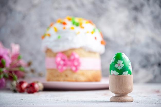 Вид спереди вкусный пасхальный пирог с расписным зеленым яйцом внутри яичной чашки на белой поверхности десерт весна сладкая пасха красочный пирог богато украшенный мульти группа