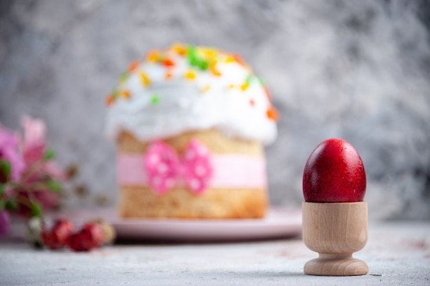 Вид спереди вкусный пасхальный пирог с расписным красным яйцом внутри яичной чашки на белой поверхности десерт весна сладкая пасха красочный пирог богато украшенный мульти группа