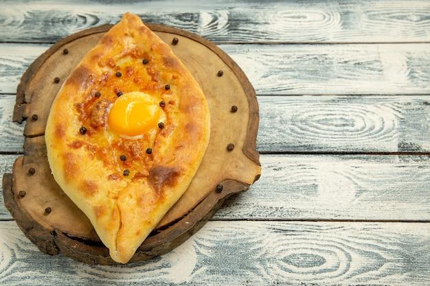 灰色の素朴な机の上で焼いた正面のおいしい卵パン