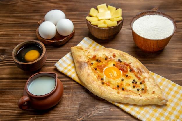 Vista frontale gustoso pane all'uovo appena sfornato con latte e formaggio sulla pasta marrone scrivania cuocere il pane panino uovo