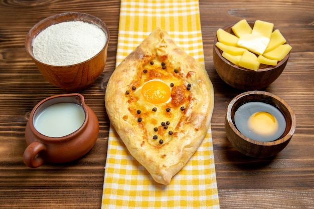 正面図オーブンで焼きたてのおいしい卵パンとミルクとチーズを木製の机の上に置いた生地焼きパンパンの卵