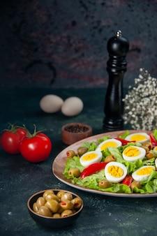 正面図おいしいエッグサラダは、暗い背景にグリーンサラダとオリーブで構成されています