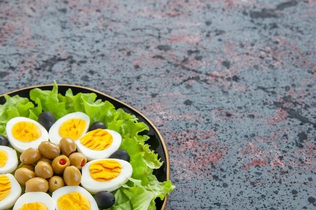 正面図おいしいエッグサラダは、明るい背景にグリーンサラダとオリーブで構成されています