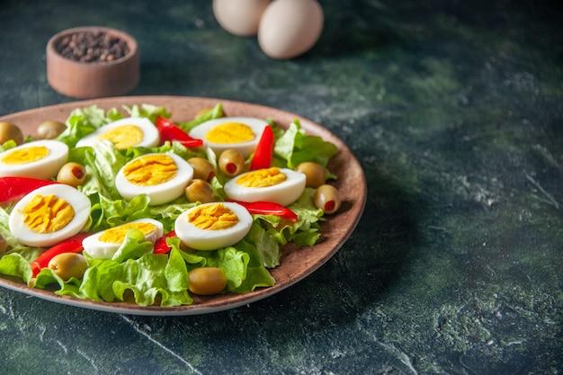 正面図おいしいエッグサラダは、暗い背景にオリーブとグリーンサラダで構成されています
