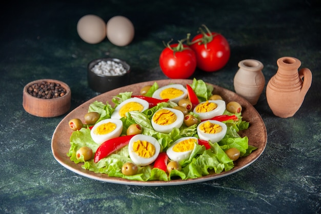 正面図おいしいエッグサラダは、紺色の背景にオリーブとグリーンサラダで構成されています