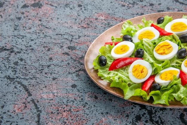 明るい背景にグリーンサラダとオリーブの正面のおいしいエッグサラダ