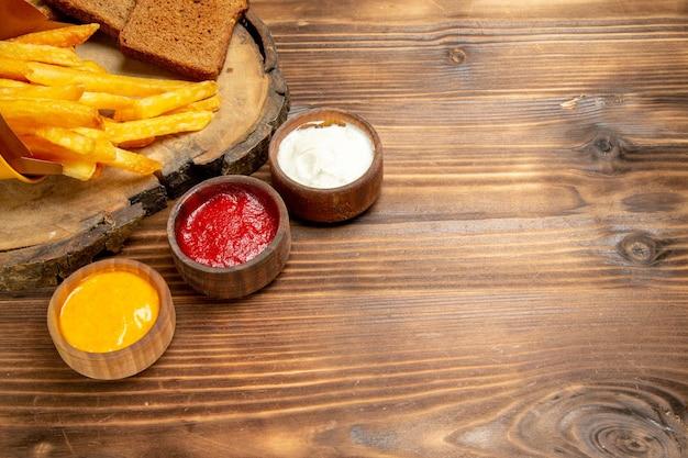 Vista frontale gustose patatine fritte con condimenti su pane marrone da scrivania patate fast-food