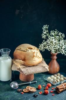 Vista frontale gustoso pane fresco con noci e latte su superficie scura