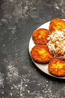 Vista frontale gustose cotolette fritte con riso cotto sul pasto di piatto di carne foto scrivania scura