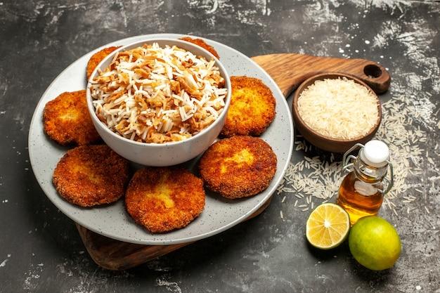 Vista frontale gustose cotolette fritte con riso cotto sul piatto di polpetta di carne superficie scura
