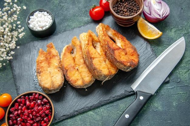 Vista frontale gustoso pesce fritto sulla superficie blu scuro pasto pepe carne frittura frutti di mare frutti di mare insalata piatto cucina