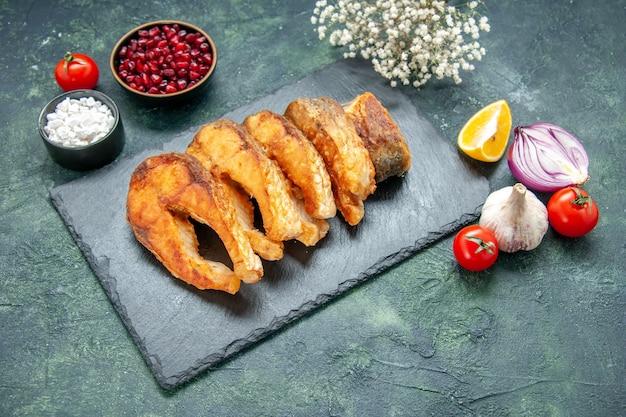 Vista frontale gustoso pesce fritto su superficie scura pasto pepe cucina frittura frutti di mare carne di mare cibo piatto di insalata