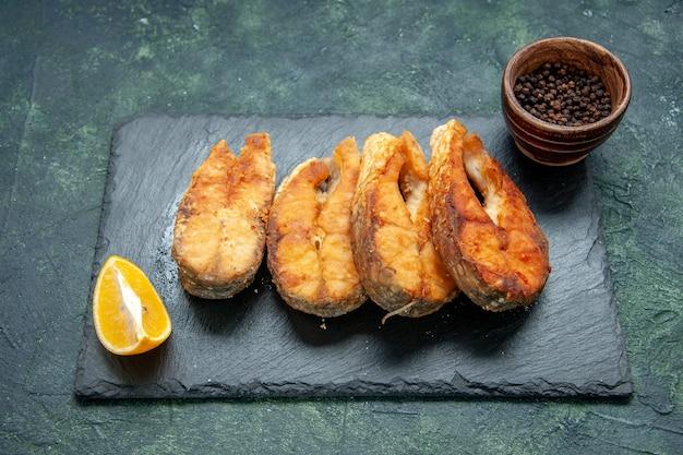 Vista frontale gustoso pesce fritto su superficie scura pasto pepe carne cucina frittura frutti di mare frutti di mare piatto di insalata di frutti di mare