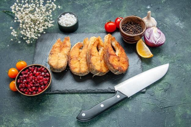 Vista frontale gustoso pesce fritto sulla superficie scura pasto pepe carne frittura frutti di mare frutti di mare insalata piatto cucina