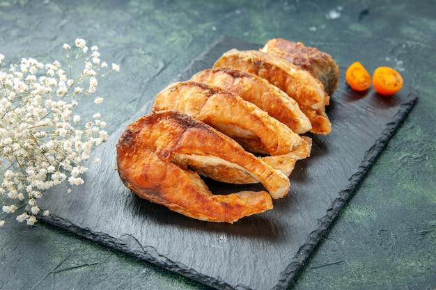 Vista frontale gustoso pesce fritto sulla superficie scura pepe piatto di cucina insalata frittura pasto frutti di mare carne di mare cibo