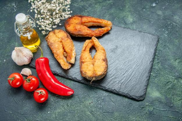 正面図暗い背景にトマトと赤唐辛子を添えたおいしい揚げ魚の調理サラダミールフードシーフード肉海の皿フライ