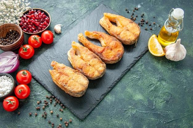 Vista frontale gustoso pesce fritto con pomodori sulla superficie blu scuro cucina piatto cibo insalata friggere pasto frutti di mare pepe carne di mare