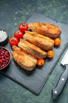 Vista frontale gustoso pesce fritto con pomodori sulla superficie blu scuro cibo insalata pasto carne frutti di mare mare cucina frittura piatto