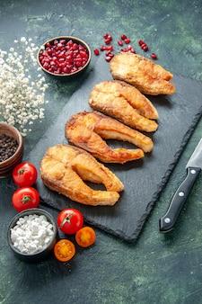 Vista frontale gustoso pesce fritto con pomodori sulla superficie scura piatto cibo insalata frittura carne mare cucina pasto frutti di mare