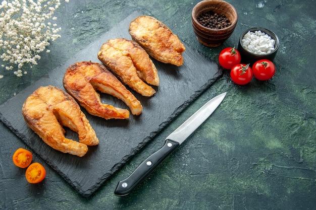 Vista frontale gustoso pesce fritto con pomodori sulla superficie scura piatto cibo insalata friggere carne pepe di mare cucinare pesce pasto