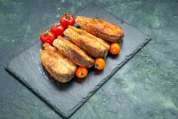 Vista frontale gustoso pesce fritto con pomodori sulla superficie scura cibo pasto pepe carne frittura frutti di mare insalata di mare piatto di cottura