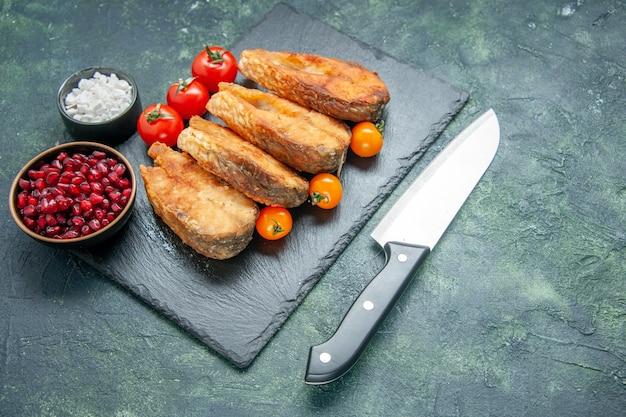 Vista frontale gustoso pesce fritto con pomodori sulla superficie scura cibo insalata pasto carne frutti di mare mare cucina frittura piatto