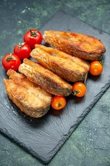 Vista frontale gustoso pesce fritto con pomodori sulla superficie scura cibo insalata pasto pepe carne frutti di mare piatto di mare cucina frittura