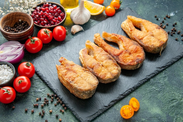 正面図暗い表面にトマトを添えたおいしい揚げ魚の調理皿サラダフライミールシーフードペッパー海の肉料理