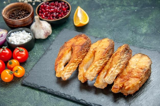 Vista frontale gustoso pesce fritto con pomodori e condimenti sulla superficie scura frutti di mare piatto insalata di frutti di mare frittura di carne di cottura
